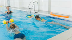 Instructor and child doing exercises in swimming pool. Coach teaches girls to Stock Footage