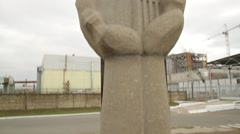 Chernobyl monument and reactor in background before New sarcophagus slides over Stock Footage