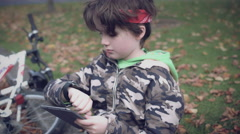 4k Sport Outdoor Child with Bicycle Working on Tablet, dolly shot Stock Footage