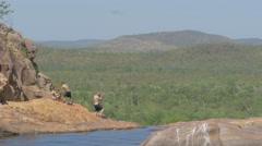 3 Tourist stand on the edge of Gunlom Falls and take photos, Kakadu, Australi Stock Footage