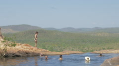 Tourists enjoy a swim in the infinity pool at the top of Gunlom Falls, Kakadu Stock Footage