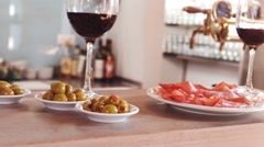 Glass of red wine and snacks on bar counter Stock Footage