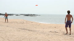 Man playing Frisbee on the beach Stock Footage