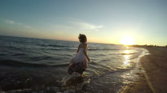 Girl in a fluttering dress runs along the surf line Stock Footage