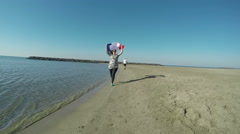 Woman with the French flag runs along the seashore Stock Footage