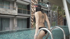 Sexy brunette woman in crochet swimsuit by the pool Stock Footage