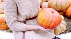 Young woman hanging pumpkin for jack o'lantern Stock Footage