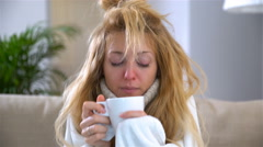 A woman with fever and a runny nose sneezes loudly and drinks hot drink. Stock Footage
