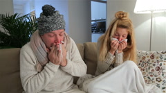 Pair with fever and runny noses sneezes loudly sitting in the living room. Stock Footage