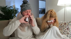 Sick pair with runny noses using nasal spray and sneezes loudly in living room. Stock Footage