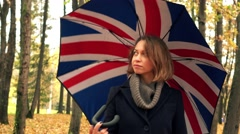 Pensive young woman walking with British flag-like umbrella in autumn park alley Stock Footage