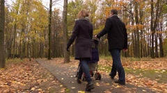 Young family walking with baby stroller in autumn park. 4K steadicam shot Stock Footage