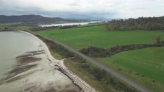 Static aerial of Dunalley Bay and cars passing by on Arthur Highway, Tasmania Stock Footage