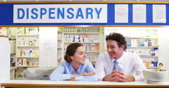 Smiling pharmacists leaning at counter in pharmacy Stock Footage
