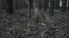Young man in a red shirt going through coniferous forest. Back view Stock Footage
