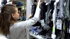 Girl Brunette Get Shopping At The Mall - Clothes On The Trempels Stock Footage