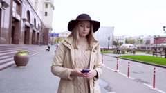 Young woman walking down moscow street, wearing broad brim hat Stock Footage