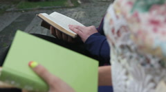 Couple reading a books on a bench Stock Footage