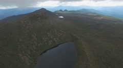 Forward flight above Lake Esperance passing clouds at Hartz Mountains, Tasmania Stock Footage