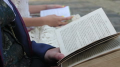 Man and young women reading a books on a bench Stock Footage