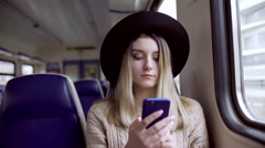 Young woman typing message on her phone and smiling, sitting in electric train Stock Footage
