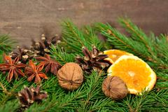 Star anise, nuts, cones, dried oranges and spruse branch on a wooden board Stock Photos