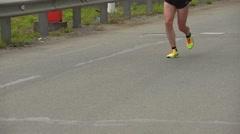 Legs of an athlete on marathon race running on camera. slow motion Stock Footage