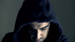Young hooded man looks menacingly at the camera Stock Footage