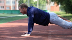 Man doing workout in an outdoor stadium. Morning gymnastics Stock Footage
