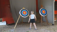 Boy shorts considering the target for which to shoot a bow Stock Footage