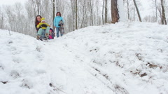 Mother with a little girl rides a sled from a hill Stock Footage