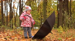 Little girl playing with big umbrella in autumn park. Bad weather concept. 4K Stock Footage