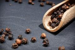 Black pepper on rustic stone background. Overhead view food photography. Stock Photos