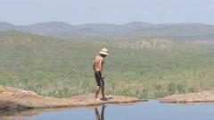 Man walks along the edge of the cliff at Gunlom Falls, Kakadu Stock Footage