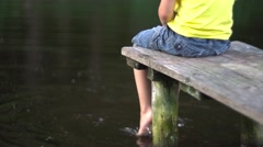 Boy sitting on bridge at pool Stock Footage