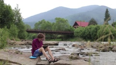 Young man sits on a rock in the river and draws of landscape Stock Footage