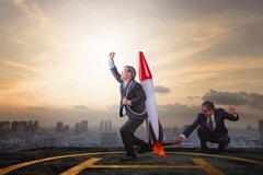 Two business man playing rocket toy on high building roof with sky scraper ba Stock Photos