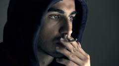 Young hacker with hood smoking a cigarette thinking about his next strategy Stock Footage