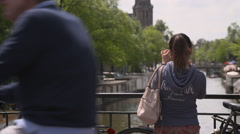 Female tourist taking photos with her smart phone from a bridge Stock Footage
