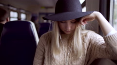Teen hipster girl listening music and typing message on phone in electric train Stock Footage