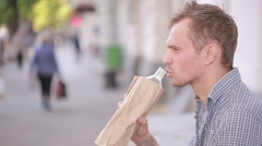 Slovenly man drinking alcohol in the street. beer in a paper bag. Stock Footage