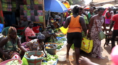 Women in city market selling and buying goods - Guinea Africa Stock Footage
