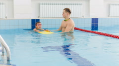 Instructor and child doing exercises in swimming pool. Coach teaches boy to swim Stock Footage