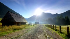 Rocky road between cottages in the valley Chocholowska at sunrise, Tatras Stock Footage