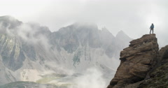 Mountaineer Climbing Rock Stack in Stormy and Windy Conditions. Stock Footage