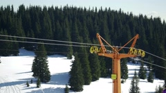 Chair skilift with skiers going over the slopes and mountain ridges with forest  Stock Footage