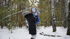 Mother playing with baby in winter Park. mom throws the kid up Stock Footage