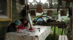 Children draw in the album on the porch of rural house 2.mp4 Stock Footage