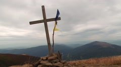 Wooden cross with ragged flag on a mountaintop Stock Footage