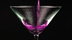 Pouring crimson cocktail in martini glass on black background Stock Footage